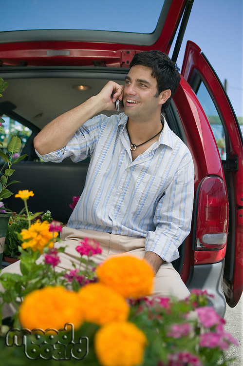 Man Using Cell Phone at the Plant Nursery