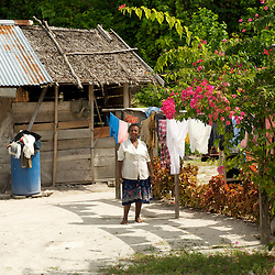 Papua woman drying laundry in front of her house.