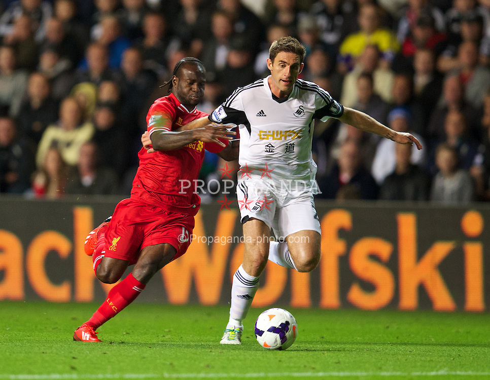SWANSEA, WALES - Monday, September 16, 2013: Liverpool's Victor Moses in action against Swansea City's Angel Rangel during the Premiership match at the Liberty Stadium. (Pic by David Rawcliffe/Propaganda)