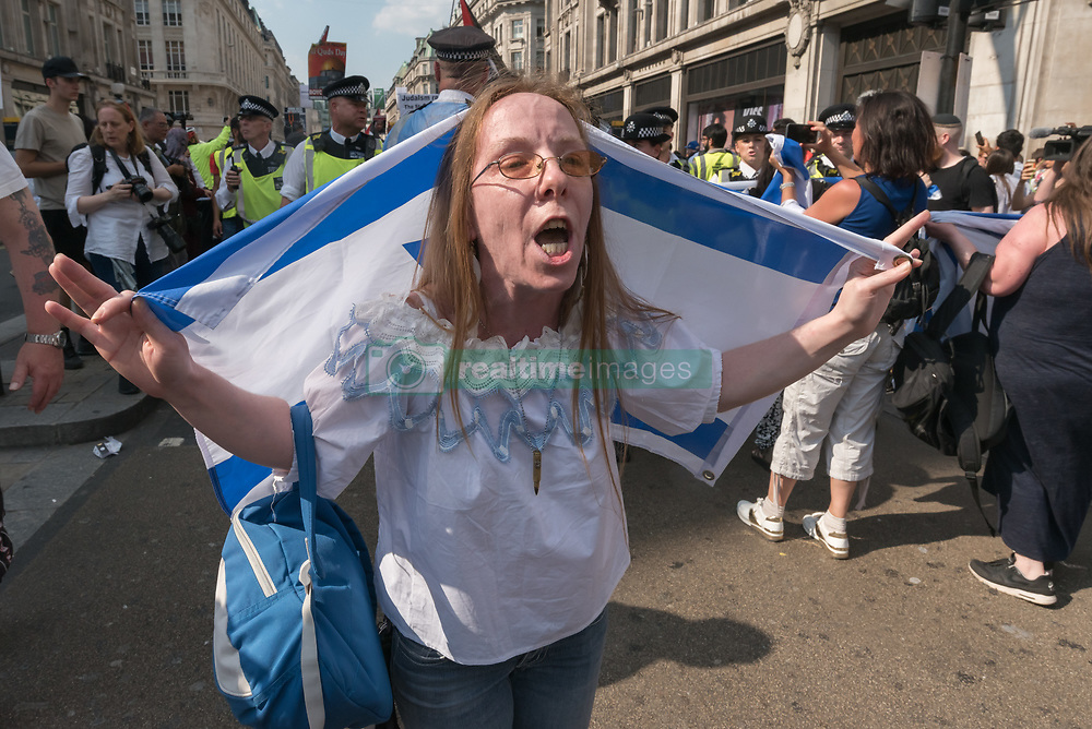 June 18, 2017 - London, UK - London, UK. 18th June 2017. A handful of protesters had stood across the road and shouted insults at the Al Quds march as it formed up close to the BBC. As the march came close to Oxford Circus, around 30 Zionists holding Israeli flags moved to block the road. The marchers stopped, commenting that not being content with occupying Palestine, Zionists now wanted to occupy Regent St, and waited patiently for police to clear the road. Eventually police made the protesters move on, but they only went a few yards into Oxford St before blocking the route again. Peter Marshall ImagesLive (Credit Image: © Peter Marshall/ImagesLive via ZUMA Wire)