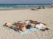 group of sunbathers lying on beach Miami USA