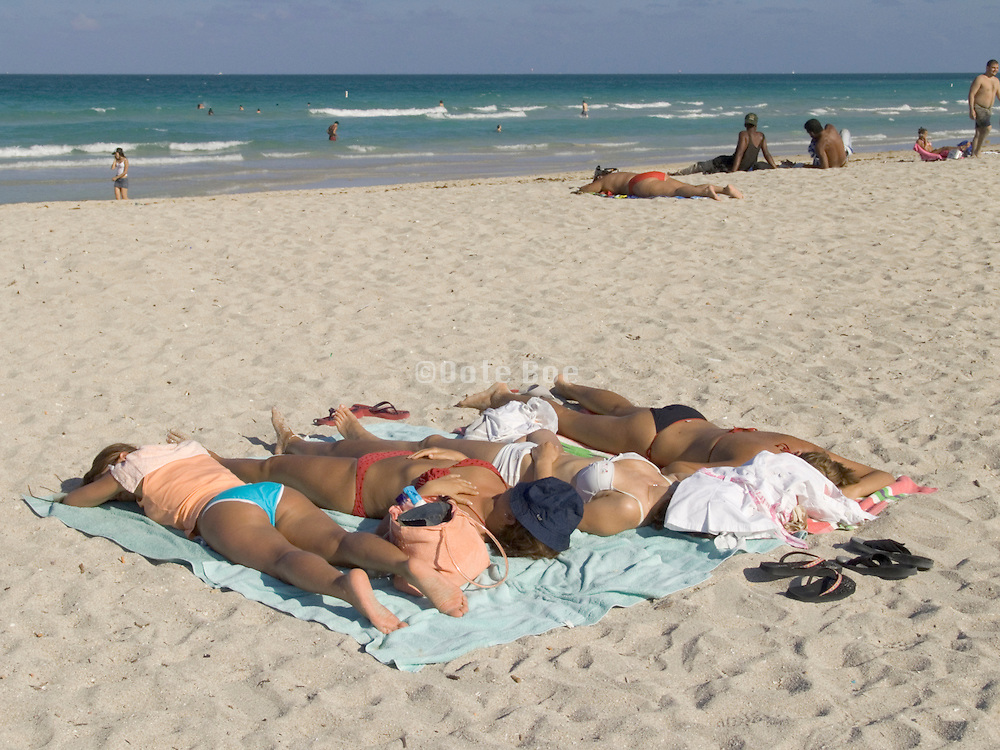 group of sunbathers lying on beach Miami USA