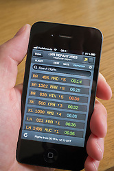 Man using flight tracking App to look at live flight departures board at Heathrow Airport on an iPhone 4G