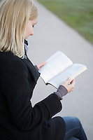 Blonde woman sits reading book outside on path