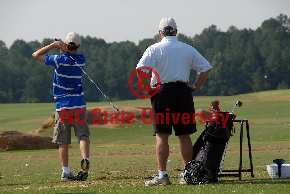 Mens head golf coach Richard Sykes (r) watches a camper's drive at the Lonnie Poole Golf Course. PHOTO BY ROGER WINSTEAD