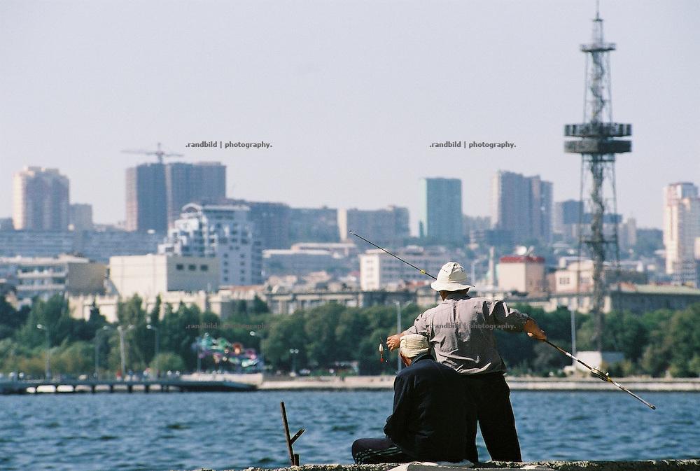 Im Hafen der aserbaidschanischen Hauptstadt Baku angeln auf einer Kaimauer alte Herren. Das Wasser ist von der Ölförderung im Kaspischen Meer verschmutz. Entsprechend keine Fische gehen ihnen an den Haken...Fishermen in the harbour of Baku, Aserbaijan.