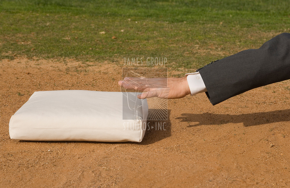Arm of a business man about to touch a baseball base in a baseball diamond
