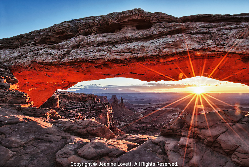 Sun just came up creating a starbust pattern under Mesa Arch in Canyonlands National Park, Utah, USA.