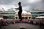 Street performer thrills the crowd with his knife juggling act whilst in a slack line. Covent Garden plaza in the West End of London.