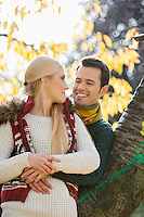 Happy young man hugging woman while leaning on tree trunk during autumn in park