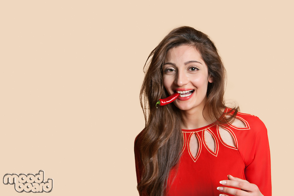 Portrait of a beautiful young woman with red chili pepper in mouth over colored background