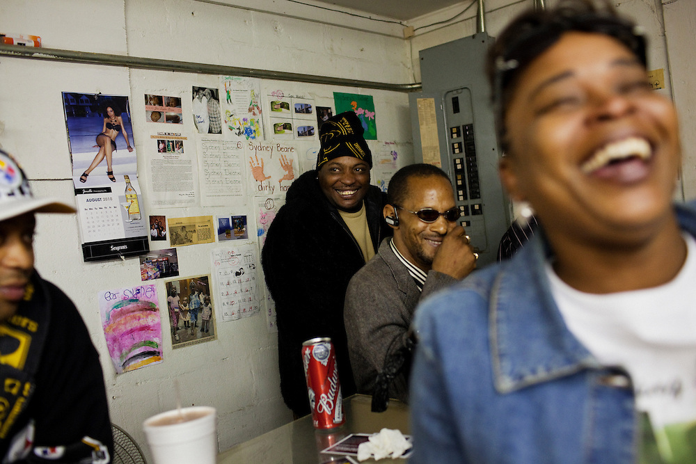 """Smitty,"" (middle), Dwight Harris (sunglasses) and other friends of Demetrius ""Butta"" Anderson, 18, clown around in Hoover's Convenience Store after hours of drowning their sorrows following Butta's funeral in the Baptist Town neighborhood of Greenwood, Mississippi on Friday, November 5, 2010. Butta was shot and killed on October 27, 2010."