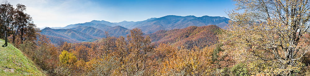 Black Mountains Overlook, elevation 3892 feet, on Milepost 342.0 of the Blue Ridge Parkway, North Carolina, USA.  The Black Mountains are the highest mountains in the Eastern United States. Located in western North Carolina, mostly within Pisgah National Forest, the Blacks are part of the Blue Ridge Province of the Southern Appalachian Mountains. The range takes its name from the dark appearance of the Red Spruce and Fraser Fir trees on the upper slopes which contrasts with the brown (during winter) or lighter green (during the growing season) appearance of the deciduous trees at lower elevations. The Eastern Continental Divide, which runs along the eastern Blue Ridge crest, intersects the southern tip of the Black Mountain range. Mount Mitchell State Park protects the range's highest summit (6,684 feet or 2,037 meters). The Blue Ridge Parkway passes along the range's southern section, and is connected to the summit of Mount Mitchell by North Carolina State Route 128. The Black Mountains are mostly located in Yancey County, although the range's southern and western extremes are part of Buncombe County. Panorama stitched from 5 overlapping photos.