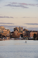 A lone paddleboarder cruises the Victoria Inner Harbour at sunset.