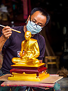 31 JULY 2018 - BANGKOK, THAILAND: An artisan on Phlap Phla Chai Road in Chinatown paints a statue of a revered Buddhist monk. Bangkok's Chinatown district is one of the largest Chinatowns in the world. It was established in 1781 when Siamese King Rama I gave the Chinese community in Bangkok land outside of Bangkok's city walls so he could build his palace (what is now known as the Grand Palace). Chinatown is now the heart of the Thai-Chinese community. About 14% of Thais have Chinese ancestry.    PHOTO BY JACK KURTZ