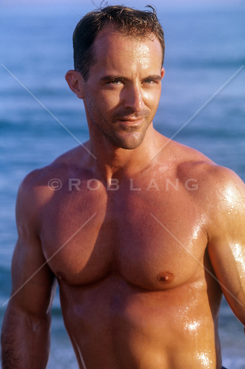 sexy shirtless man at the beach with wet smooth skin