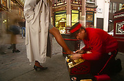 A 1990s businesswoman in the City of London, the capital's financial district, puts one shoe for a shoeshine in Leadenhall Market, on 15th April 1993, City of London, England.