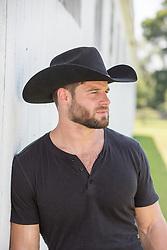 Portrait of a hot rugged cowboy by a barn