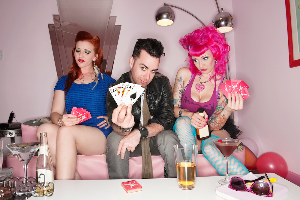 Portrait of man holding playing cards with women sitting besides him