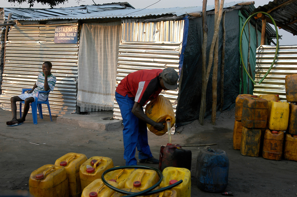 Men filling jerry cans of gasoline to sell in the market place. Along with Nigeria, Angola is Africa's largest producer of oil. After decades of war, the country is undergoing a vast reconstruction program..Luau, Moxico Province, Angola. 27/07/2008..Photo © J.B. Russell