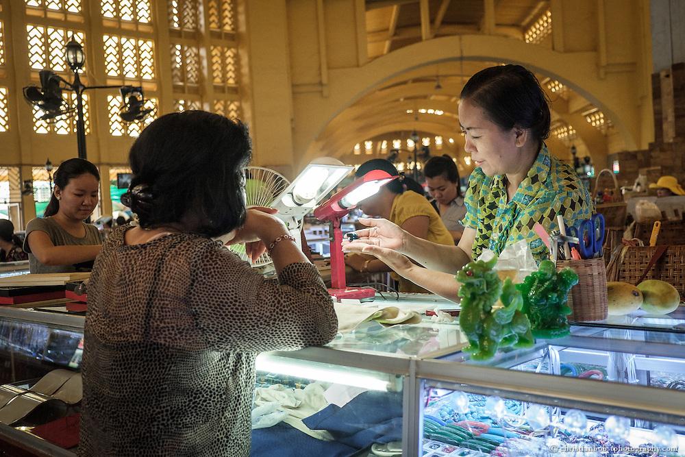 Eine Markthändlerin im Central Market Phnom Penhs begutachtet einen Edelstein, welcher ihr von einer Kundin zum Kauf angeboten wird.