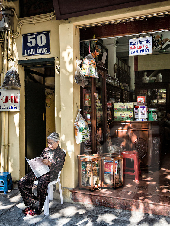 A woman sits outside a shop along Lan Ong 'traditional medicine street' in Hanoi's Old Quarter, Vietnam, Southeast Asia