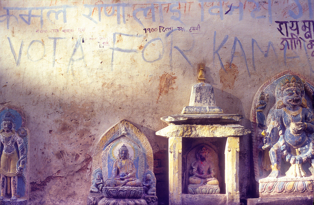 Buddhist and Hindu icons and political graffiti on a wall at the Swyambhunath temple complex (also known as The Monkey Temple) on a hill overlooking Kathmandu, Nepal.