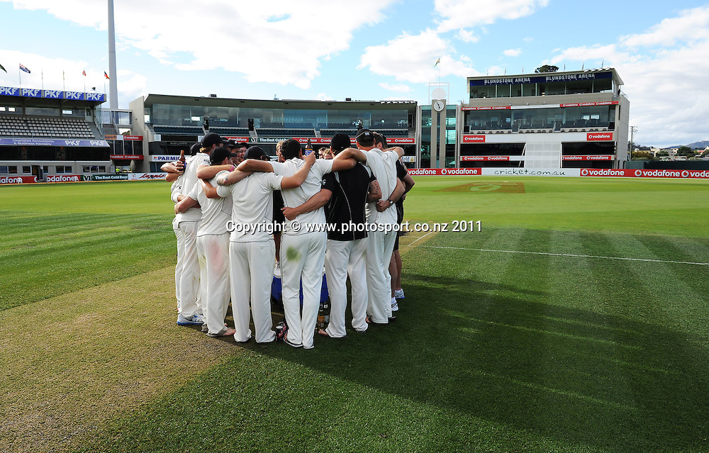 New Zealand players and coaching staff huddle together in the middle of the wicket after a famous victory over Australia on Day 4 of the second cricket test between Australia and New Zealand Black Caps at Bellerive Oval in Hobart, Monday 12 December 2011. Photo: Andrew Cornaga/Photosport.co.nz
