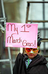 17 Feb 2015. New Orleans, Louisiana.<br /> Fat Tuesday. Mardi Gras Day. Faces in the crowd. A young child holds up a sign revealing that it's his first Mardi Gras.<br /> Photo; Charlie Varley/varleypix.com