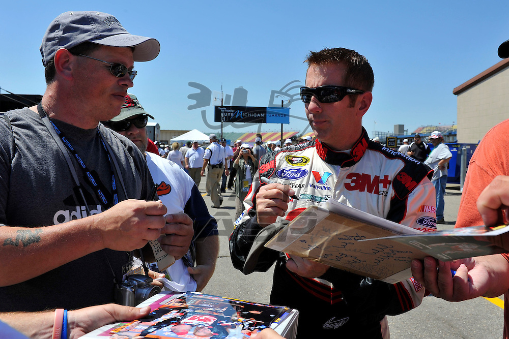 Brooklyn, MI - JUN 15, 2012: Greg Biffle (16) signs autographs in the garage during practice for the Quicken Loans 400 race at the Michigan International Speedway in Brooklyn, MI.