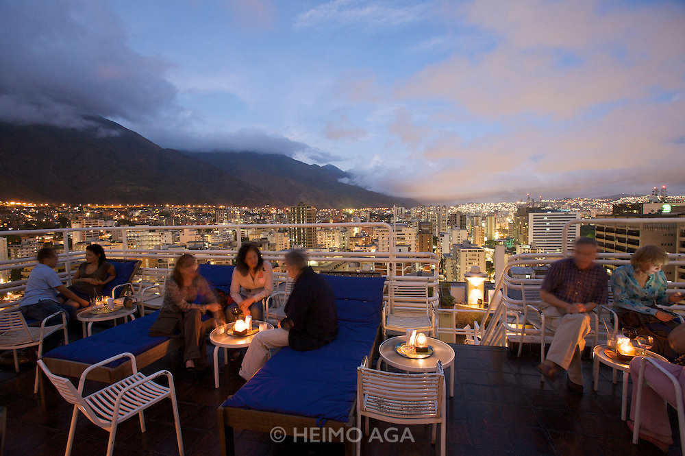 Wealthy Venezoelans and tourists enjoying a spectacular sunset view over downtown Caracas from 360º Roofbar at Hotel Altamira Suites.