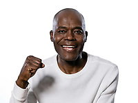 Close-up portrait of an excited afro American man clenching fist in studio on white isolated background