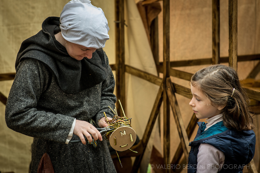 A woman teaches a modern anglo-saxon girl how to make a little wicker basket. It's been 950 years since King Harold got an arrow in the eye at the Battle of Hastings. A group of re-enactors set up a camp near Apsley House in Hyde Park, London, to show their weapons, games and living arrangements.
