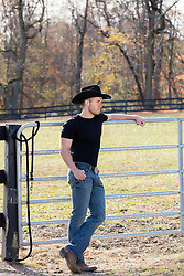 cowboy leaning on a gate