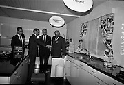 Irish Furniture Fair..1966..27.09.1966..09.27.1966..27th September 1966..Today saw the opening of the Irish Furniture Fair at the Intercontinental Hotel in Dublin. The fair is to promote the quality and value of furniture manufactured within Ireland...Picture shows that even kitchens were catered for at the fair, here the Minister is being shown the integrated fitting of a waste bin.