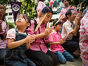 13 OCTOBER 2016 - BANGKOK, THAILAND:  A woman and her children pray for Bhumibol Adulyadej, the King of Thailand, at Siriraj Hospital Thursday morning before the King's death was announced. Thousands of people came to the hospital to pray for the beloved monarch. Bhumibol Adulyadej, the King of Thailand, died at Siriraj Hospital in Bangkok Wednesday, October 13, 2016. Bhumibol Adulyadej, 5 December 1927 – 13 October 2016, was the ninth monarch of Thailand from the Chakri Dynasty and is known as Rama IX. He became King on June 9, 1946 and served as King of Thailand for 70 years, 126 days. He was, at the time of his death, the world's longest-serving head of state and the longest-reigning monarch in Thai history.      PHOTO BY JACK KURTZ