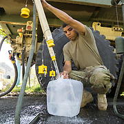 OCTOBER 25 - UTUADO, PUERTO RICO - <br /> SPC Andrea Bertarello fills up 5 gallon collapsible jugs from a water truck with 2,000 gallons of potable water parked near a baseball park in Utuado. Troops from Fort Bragg, NC, are using a water filtration system to purify water from the nearby Lago Dos Bocas.<br /> (Photo by Angel Valentin/Freelance)