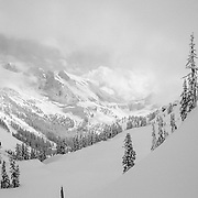 Owen Dudley makes some steep angle powder turns in the Cascades of Washington as a snow storm begins to clear.