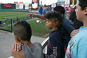 Justice Cooper, 9, of Rochester, watches as the National Anthem is performed at Frontier Field in Rochester on Friday, July 31, 2015. Students from School #17 ate dinner at the stadium, and then camped on the field Friday night.