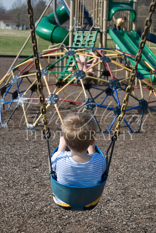 A small boy enjoys a swing at the park.