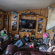 The family of  Dennis Sinnok at home in Shishmaref, Alaska, an Inupiat community of about 600 people near the Bering Strait. Shishmaref is one of at least 31 Alaska Native villages under imminent threat due to climate change, according to a 2009 report from the Government Accountability Office. Shishmaref is steadily disappearing because of erosion and flooding due to climate change. Only one quarter mile wide and two and half miles long, Shishmaref has been  grappling with rising sea levels that have eroded more than 200 feet of the village, since 1969, according to a relocation study published in February. Climate change has resulted in a reduction in the sea ice which buffers Shishmaref from storm surges. At the same time, the permafrost that the village is built on has also begun to melt, making the shore even more vulnerable to erosion.