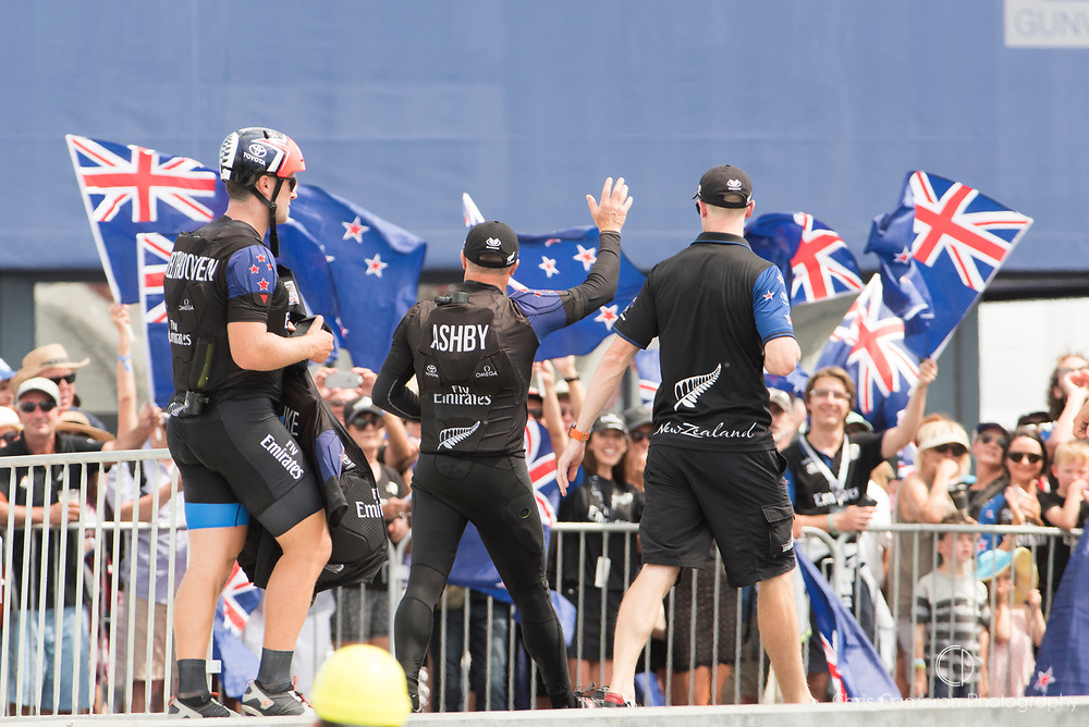 The America's Cup Village, Ireland Island, Bermuda, 17th June. Emirates Team New Zealand sailors Simon Van Velthoven (L) and Glenn Ashby (C) are cheered on by supporters as they arrive back at base after the team beat defender, Oracle Team USA in in race one and race two of the America's Cup.