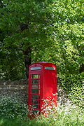 Old fashioned retro red phone box in Swinbrook, the Cotswolds, Oxfordshire, UK