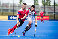 Holcombe's Richard Lane goes is watched by William Marshall of Surbiton. Holcombe v Surbiton - Semi-Final - Men's Hockey League Finals, Lee Valley Hockey & Tennis Centre, London, UK on 22 April 2017. Photo: Simon Parker