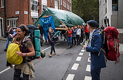 © Licensed to London News Pictures. 08/10/2019. London, UK. Extinction Rebellion activists carry a structure through the streets of Westminster. Activists have converged on Westminster for a second day, blockading roads in the area and calling on government departments to 'Tell the Truth' about what they are doing to tackle the Emergency. Photo credit: Ben Cawthra/LNP