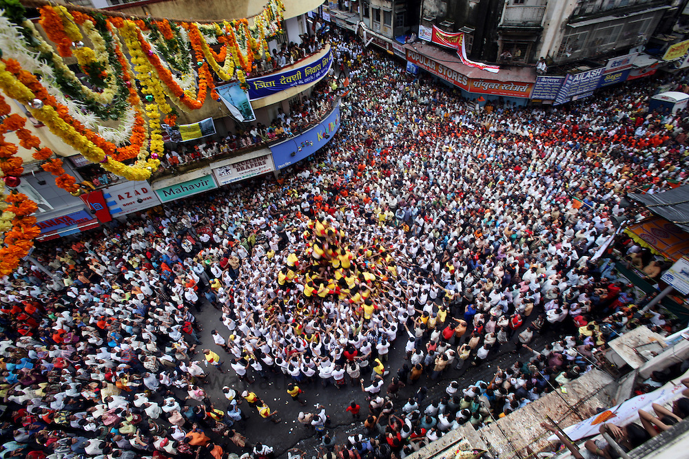 "Devotees attempt to break a pot containing butter on the occasion of  Krishna Janmashtami (birth of lord Krishna) in Mumbai, September 4, 2007. Janmashtami, which marks the birthday of Hindu god Krishna, will be celebrated across the country on September 4. As legend goes Lord Krishna as a child ate butter kept out of his reach by forming a human pyramid with his friends. Today these ""pots of butter"" contain lakhs of Indian currency as prize money. People form multistoried layers and are ready to risk serious injuries. Photographer: Prashanth Vishwanathan"