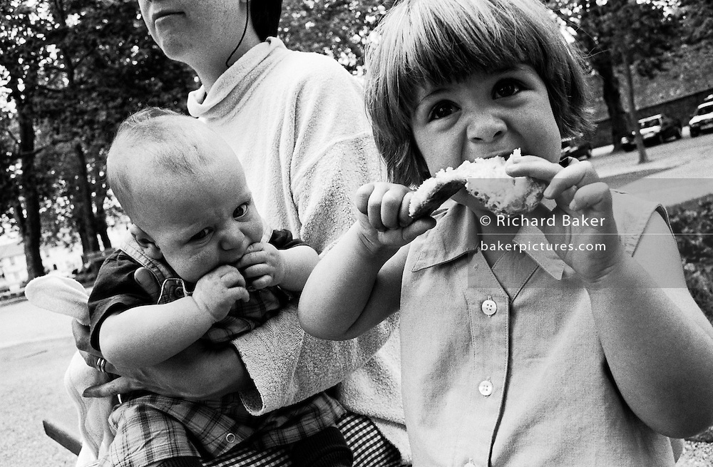 """A two and half year-old girl sits next to her three-month old baby brother, eating lunch during a day out with their mother who is seen holding on tight to the boy. With their hands up to each other's mouths, the girl takes a bite of a slice of bread sandwich. She is clearly relishing her food and has a large appetite while the boy seems to enjoy sucking on his fingers before the age where he can eat solids. From a personal documentary project entitled """"Next of Kin"""" about the photographer's two children's early years spent in parallel universes. Model released."""