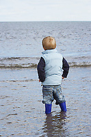 Boy (3-4) wearing wellington boots standing in ocean