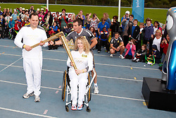 © Licensed to London News Pictures.  09/07/2012. STOKE MANDEVILLE, UK.  Gemma Collis (right), 17, from Aylesbury passes the Olympic Torch to Ian Estick (left), 44, from Milton Keynes in Stoke Mandeville Stadium, birthplace of the Paraolympics. Photo credit: Cliff Hide/LNP