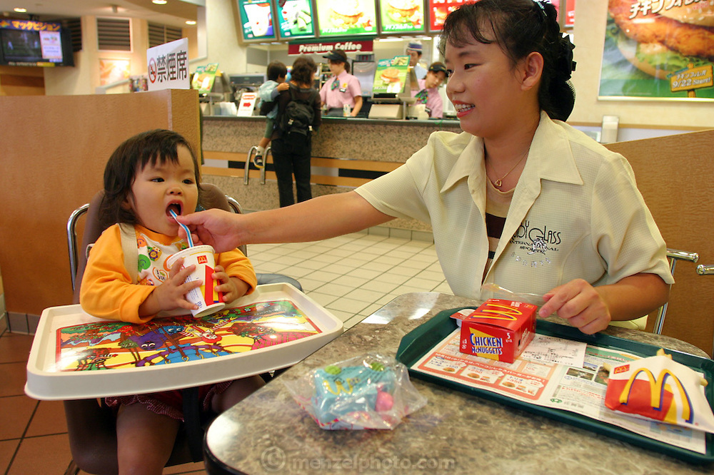 Middle class mother with daughter lunches at McDonald's on a rainy day after her daughter's preschool gym class in Kobe, Japan.